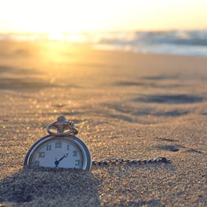 pocket watch stuck in the sand of a beach with sun setting on the ocean in the background